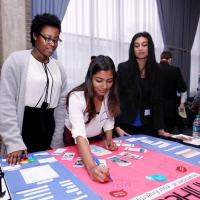 Shania Pierre, Fairooz Khondker, and Manasi Rao put the final touches on their Showcase Poster